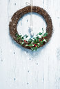 Rustic holiday garland christmas decorated with holly and berries hanging on white door Stock Photo