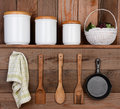 Rustic kitchen display closeup of a wall one shelf with canisters and a basket hanging on the wall below are wooden utensils Royalty Free Stock Image