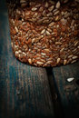Rustic loaf of bread with sunflower seeds on wood background Royalty Free Stock Images