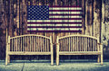 Rustic log benches with usa flag retro two wooden sit side by side outdoor against a building wall made of wooden siding a hanging Royalty Free Stock Photo