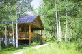 Rustic log cabin in the mountains a sitting amongst aspen forests rocky Stock Photography