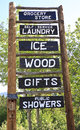 Rustic roadside advertising sign homemade timber log for rural grocery store self service laundry ice wood gifts and public Royalty Free Stock Photography