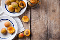 Rustic still life with apricots fresh ripe antique plates forks and napkins on wooden table vintage food Stock Photo
