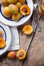Rustic still life with apricots fresh ripe antique plates forks and napkins on wooden table vintage food Stock Photography