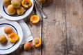 Rustic still life with apricots fresh ripe antique plates forks and napkins on wooden table vintage food Stock Photos