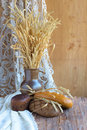 Rustic still life with bread, ears of wheat on the wooden background Royalty Free Stock Photo