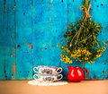 Rustic still life with two soup cups and simple bouquet on the nature blue wooden background worth village met cops of red ceramic Royalty Free Stock Photo