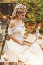 Rustic style bride sitting on stone steps at sunny autumn forest, surrounded by wedding decor. Royalty Free Stock Photo