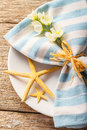 Rustic summer table setting with starfishes and blue napkin Stock Photography