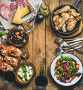 Rustic table set with meat, cheese, snacks, wine, copy space