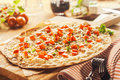 Rustic thin crust pizza on wooden cutting board close up of surrounded by fresh ingredients and cutlery Royalty Free Stock Photo