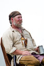 Rustic trapper with a mug of ale an old listens to stories the s during festival at the feast the strawberry moon festival Royalty Free Stock Photography