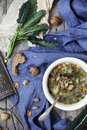 Rustic vegetables soup with legumes and lacinato kale on table with blue cloth bread walnuts Royalty Free Stock Images