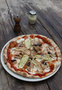 Rustic vegetarian pizza a on a wooden table in a setting Stock Photos