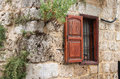 Rustic wall and window a with wooden shutter on the outside of a lebanese house Stock Photo