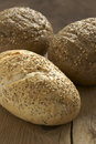 Rustic wholegrain loaves on a wooden bread board Stock Image