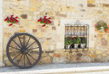 Rustic window of a peasant house decorated with flower pots and wooden wagon wheel Stock Photo