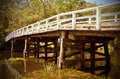 Rustic wooden bridge over river in forest Royalty Free Stock Photo