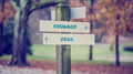 Rustic wooden sign in an autumn park with the words courage fe retro style image of a fear offering a choice of reaction and Stock Image