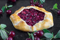 Rustical Sour Cherry Pie on Black Background with a few sour che Royalty Free Stock Photo