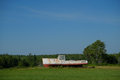 Rusting broken lobster boat in a farm field an old white large sits farmers on beautiful maine day Royalty Free Stock Photo