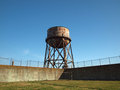 Rusting water tower stands beyond the wall and bard wire fence of grassy alcatraz s prison yard Royalty Free Stock Images