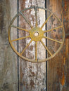Rusty Antique Cartwheel Nailed to a Barn Door. Royalty Free Stock Photo
