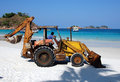 Rusty back hoe on white sand beach Royalty Free Stock Photography