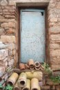 Rusty blue metal door with old red stone wall and clay tube Royalty Free Stock Photo
