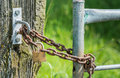 Rusty chain and a closed hardened padlock from close detailed view at wooden pole galvanized iron gate by old steel Royalty Free Stock Photos
