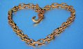 Rusty chain heart and dew a like form made by a old on a blue background that reflects the blue of the sky it suggests that hate Royalty Free Stock Image