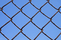 Rusty chain link fence detail of a with blue sky background Royalty Free Stock Image