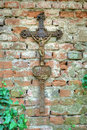 Rusty christian cross with jesus christ statue hanging on an old brick wall Stock Photos