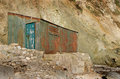 Rusty corrugated shack at the base of a cliff Royalty Free Stock Photos