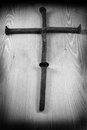 Rusty crucifix created out old railroad spikes on wooden background Royalty Free Stock Photos