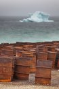 Rusty drums on arctic coast with iceberg on background fuel and chemical Stock Image