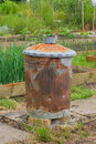 Rusty garden incinerator with plants in background for burning waste Stock Images