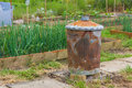 Rusty garden incinerator with plants in background for burning weeds Stock Images