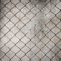 Rusty iron chain wire fence on cement wall Royalty Free Stock Photo