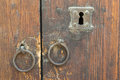 Rusty iron ring door knobs and keyhole over an old wooden grunge door Royalty Free Stock Photo