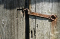 Rusty latch dilapidated wooden doors are closed Stock Photo