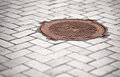 Rusty manhole in the pavement Royalty Free Stock Photo