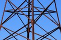 Rusty metal construction of a power line support close-up against a blue sky background Royalty Free Stock Photo