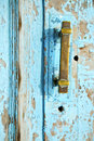 Rusty metal nail dirty stripped paint in the blue brown red wood door and knocker Stock Images