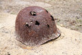 Rusty military helmet with bullet holes on grave Stock Image