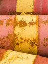 Rusty oil barrels yellow red background pattern row of steel metal and petroleum energy industry texture abstract Royalty Free Stock Images