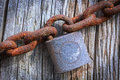 Rusty old chain and padlock an with hangs on a weathered piece of wood Royalty Free Stock Images
