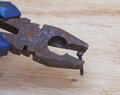 Rusty plier with nail on wood background Royalty Free Stock Photos