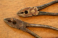 Rusty pliers two pairs of on old wooden board Royalty Free Stock Photo
