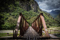 Rusty railway bridge over the river with mountains Surrounding Royalty Free Stock Photo